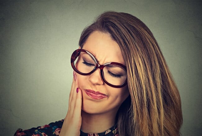 woman holding cheek caused bytooth pain