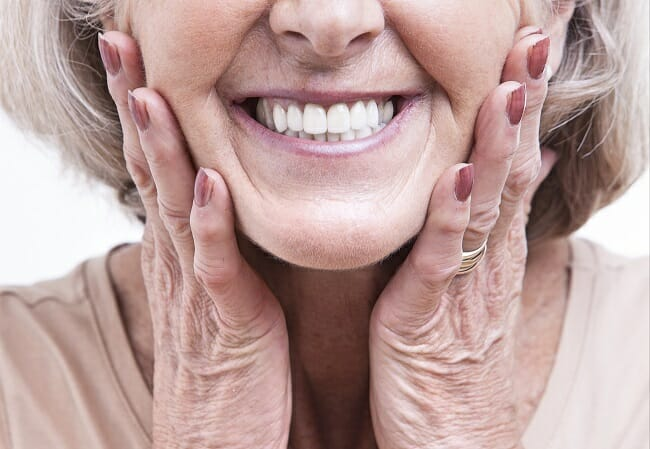 mature woman holding her face and smiling