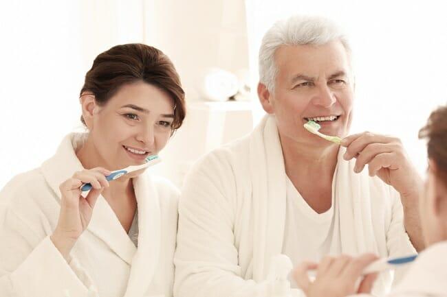 husband and wife brushing their teeth
