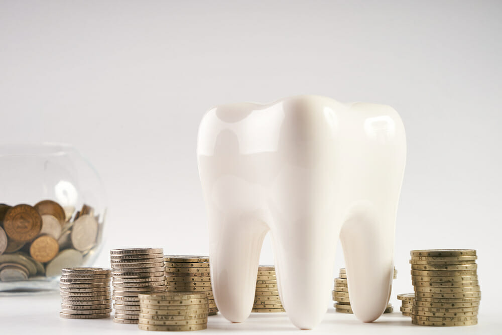 tooth next to stacks of coins