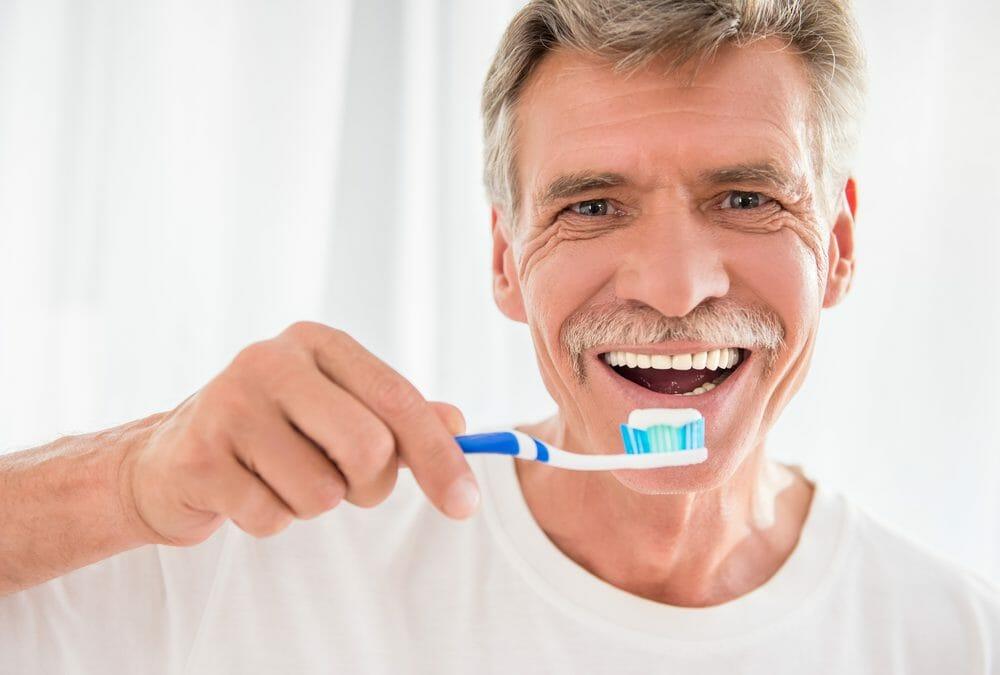 mature man brushing his teeth