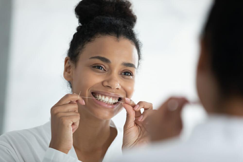 woman flossing her teeth in the mirror