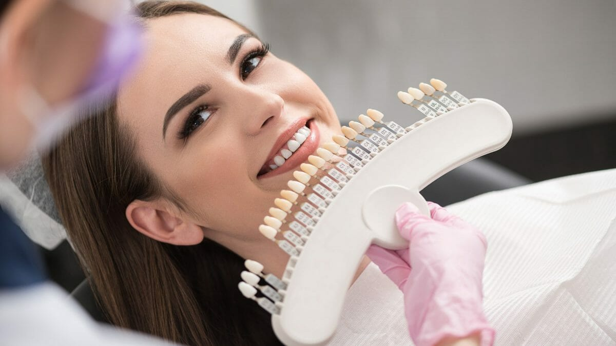 woman comparing teeth coloring at the dentist