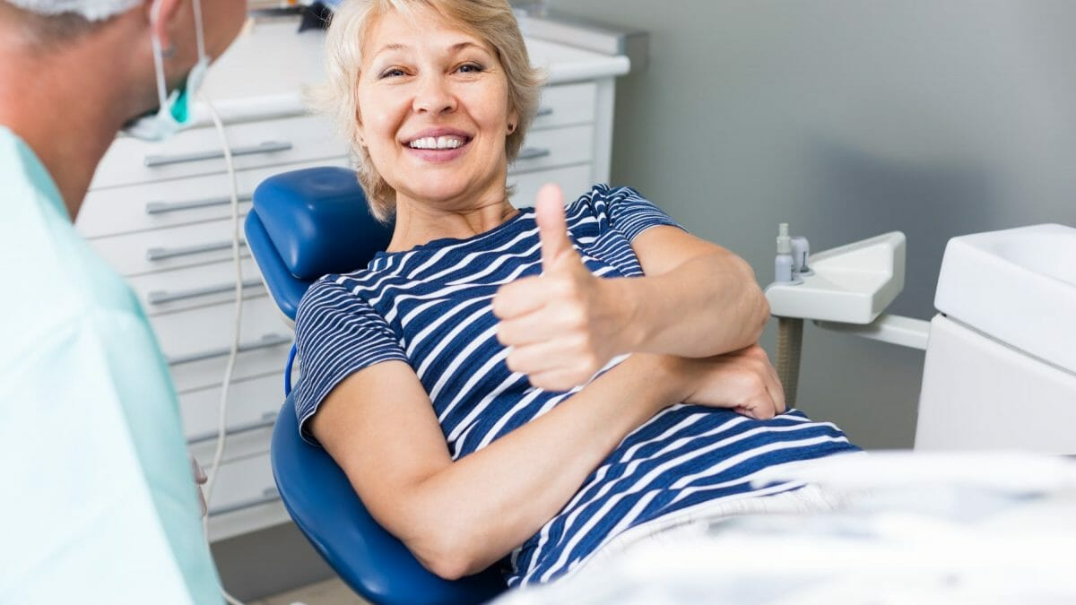 happy woman in dentist chair smiling with her thumb up