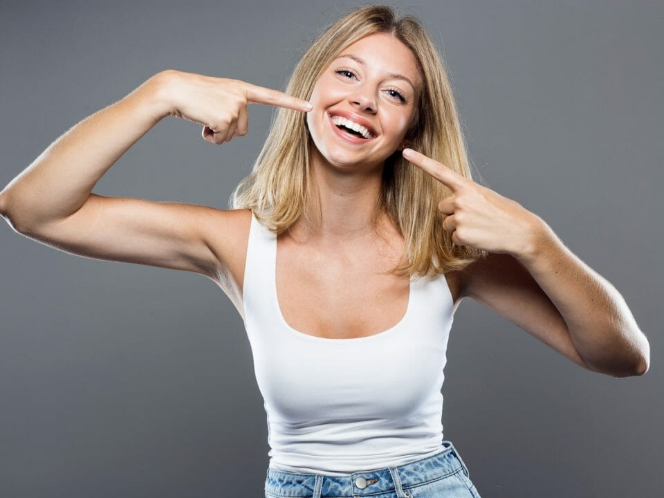 young woman pointing to teeth