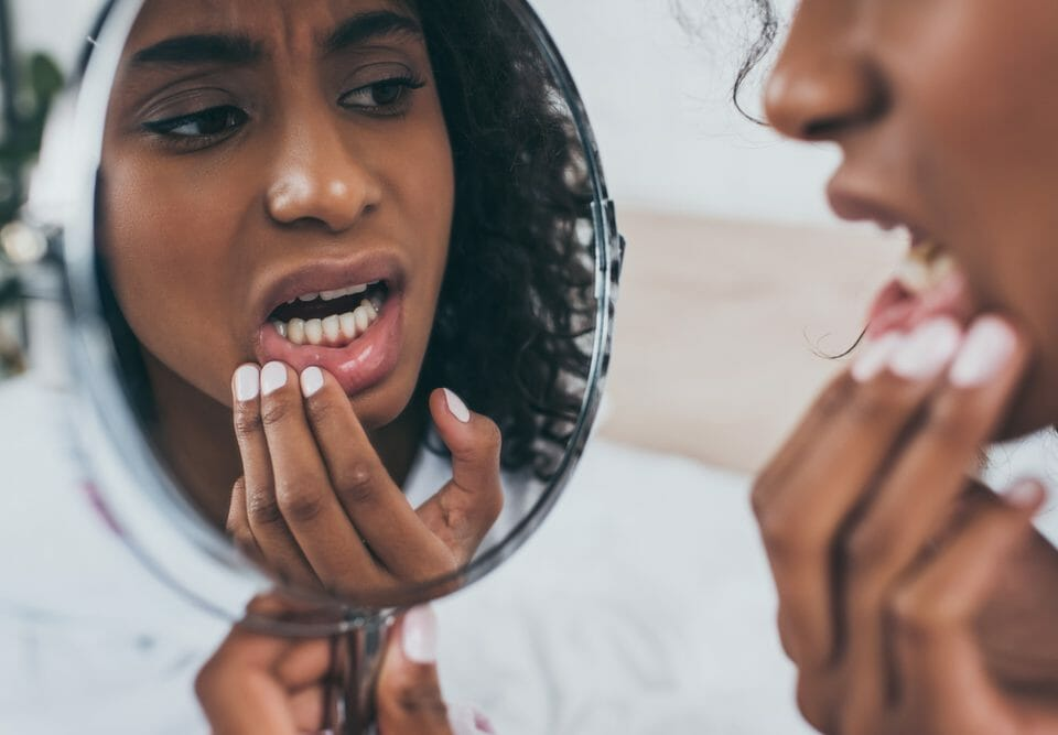 Woman looking in the mirror at her teeth.