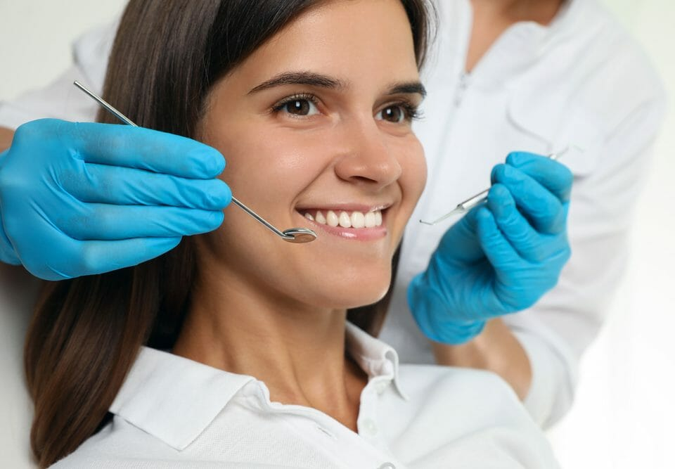 Woman Smiling with Dental Tools by Her Face